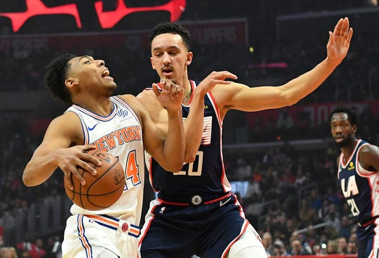 Los Angeles Clippers guard Landry Shamet (20) defends New York Knicks guard Allonzo Trier (14) as he drives to the basket in the first half of the game at Staples Center.