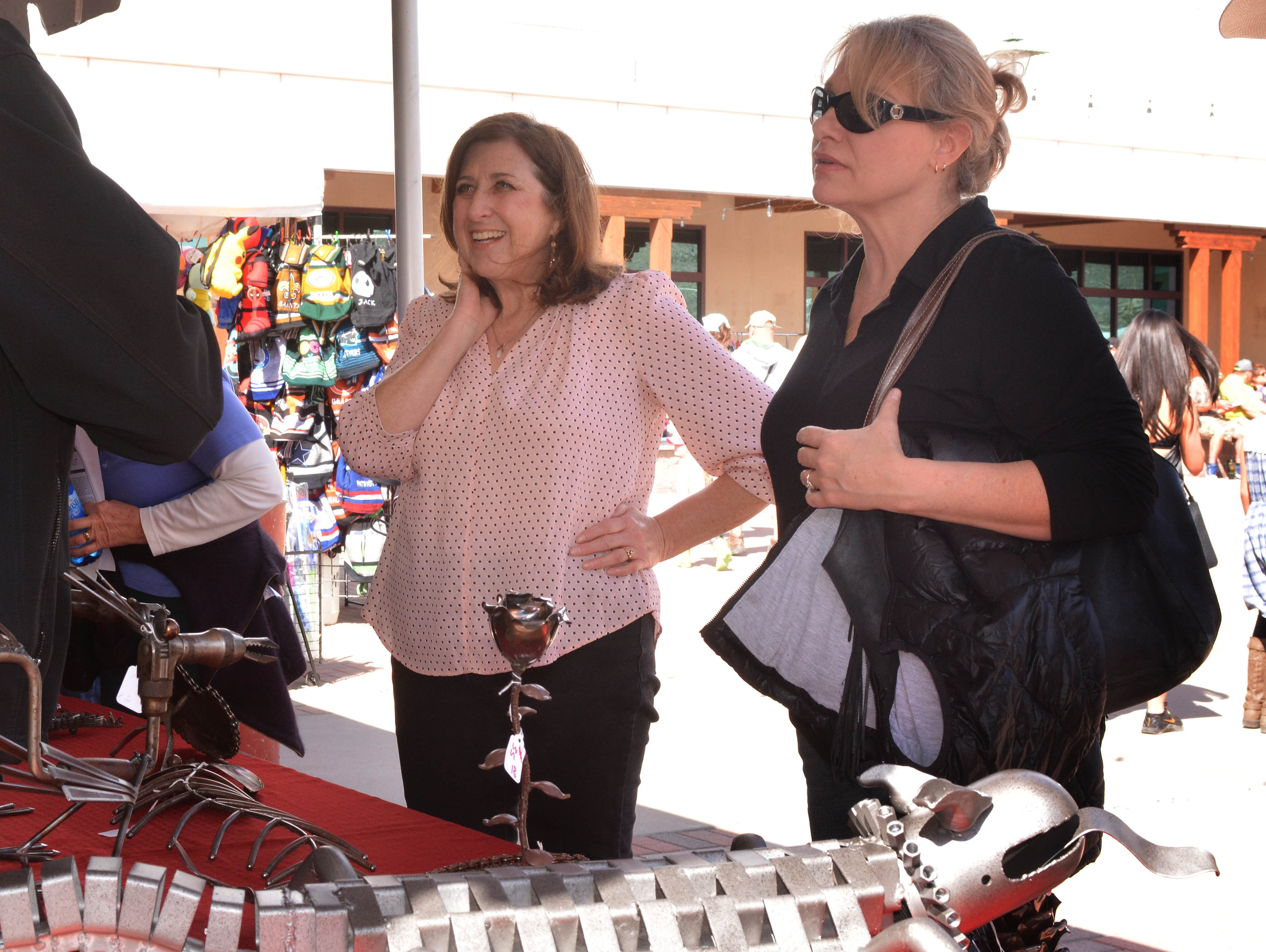 Terri Allred, left, from Broomfield, Colorado, and Monica Green, from Las Cruces, admire metal sculptures at one of the many arts and crafts vendors at the 20th annual Cowboy Days on Saturday, March 2, 2019, at the New Mexico Farm and Ranch Heritage Museum.
