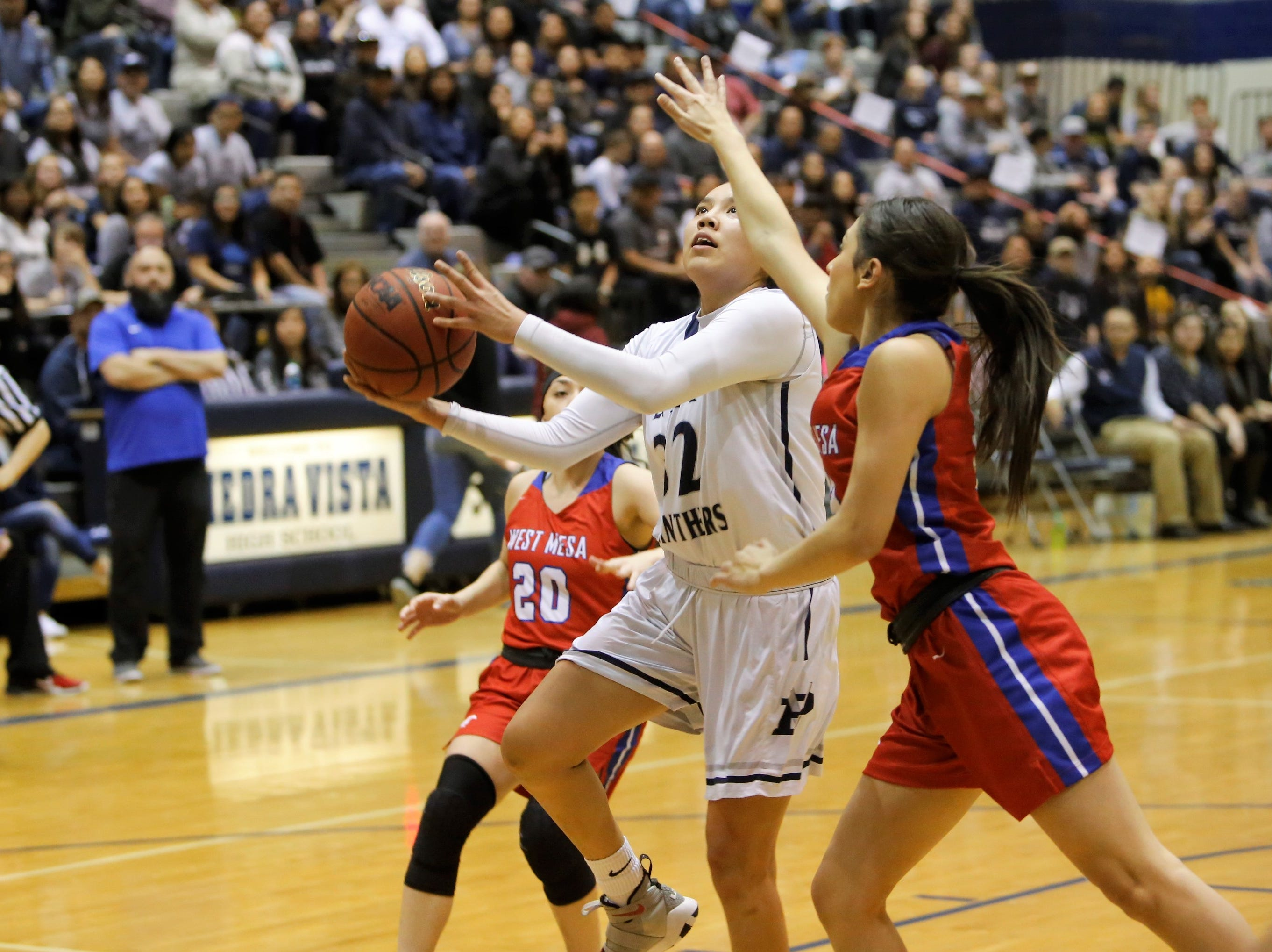 Piedra Vista's Lanae Billy drives to the basket for a fast-break layup against West Mesa's Jaden Castellano (23) during Saturday's District 2-5A tournament championship game at Jerry A. Conner Fieldhouse in Farmington.