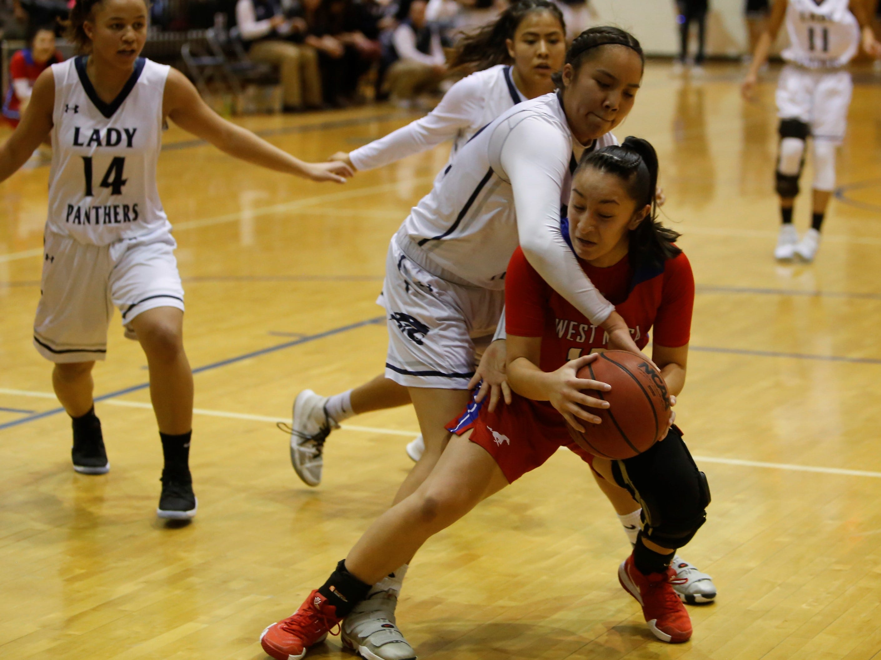 Piedra Vista's Lanae Billy fouls West Mesa's Esperanza Varoz under the basket during Saturday's District 2-5A tournament championship game at Jerry A. Conner Fieldhouse in Farmington.