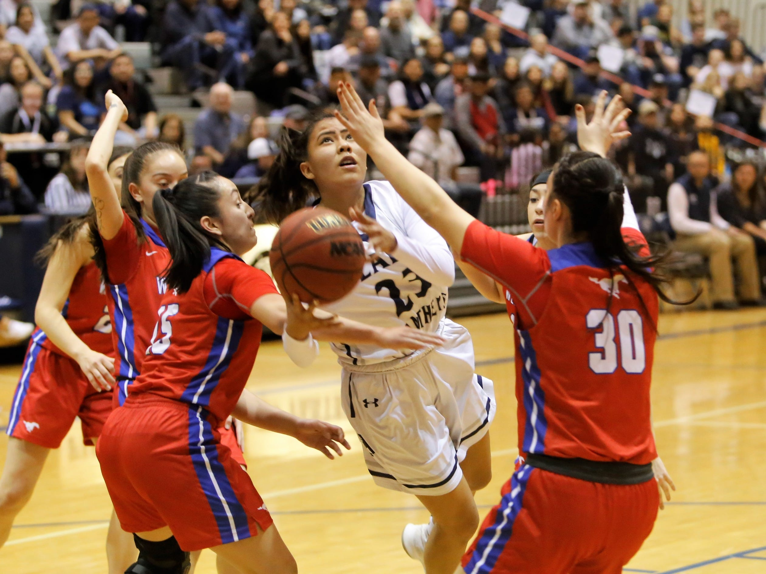 Piedra Vista's Hallie Blackie attacks the basket and gets fouled by West Mesa's Esperanza Varoz (15) during Saturday's District 2-5A tournament championship game at Jerry A. Conner Fieldhouse in Farmington.