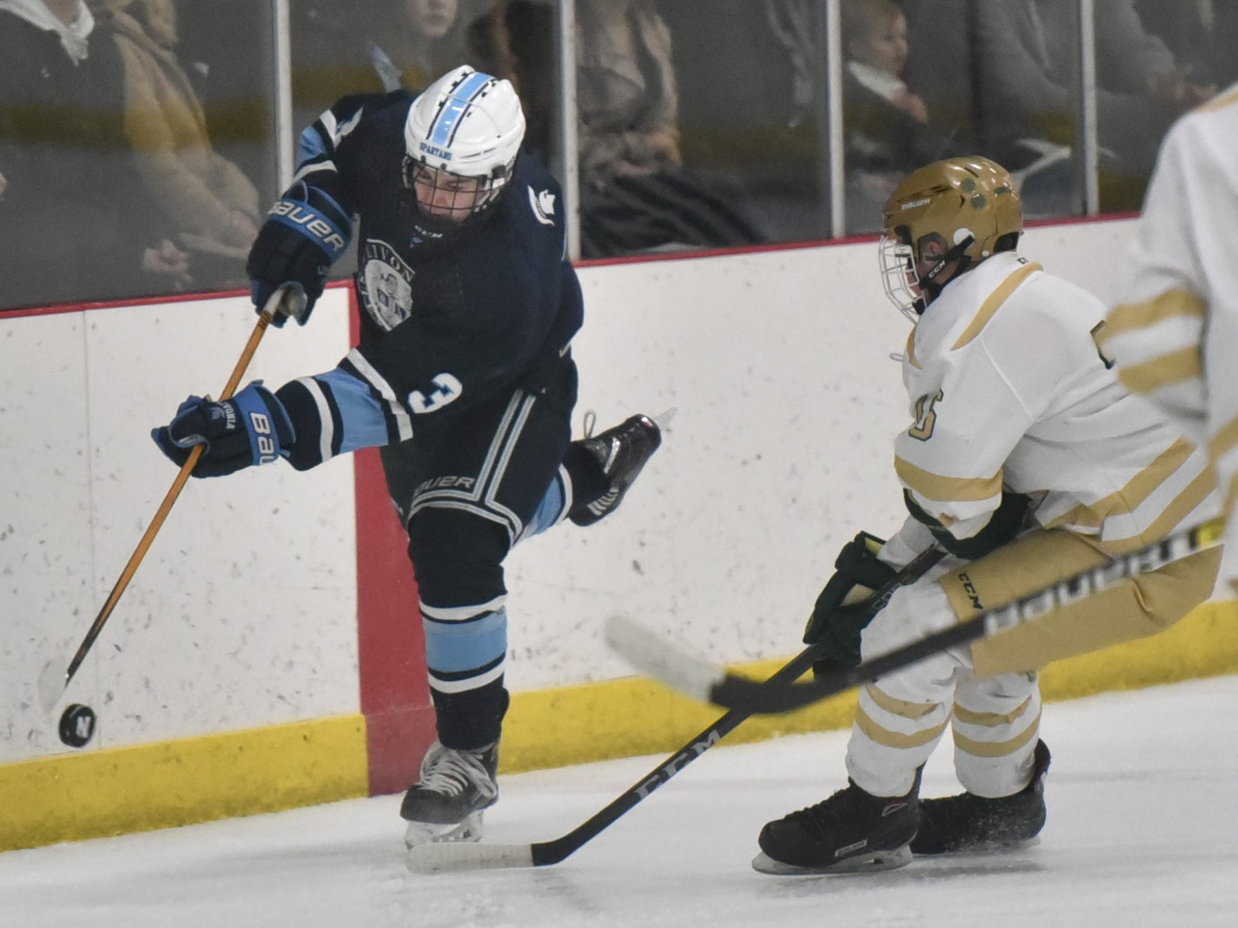 While balancing on a single skate Spartan Joe Sharkey tries to get ahold of a puck.