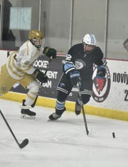 Howell Highlander Cameron Sturos gives chase to Stevenson's Josh Stuzio during the teams' March 2 playoff game at the Novi Ice Arena. Livonia Stevenson won the game 3-0 to advance in the playoffs.