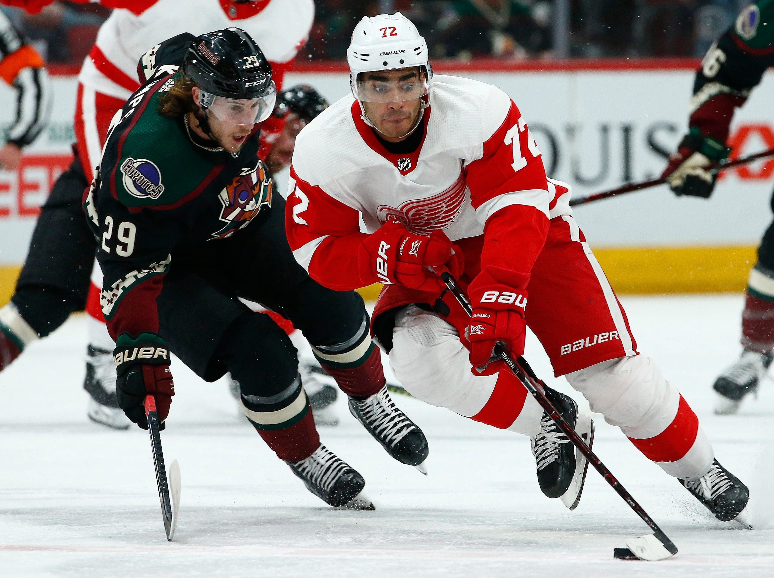 Detroit Red Wings center Andreas Athanasiou (72) skates with the puck in front of Arizona Coyotes right wing Mario Kempe (29) during the first period Saturday, March 2, 2019, in Glendale, Ariz. (AP Photo/Ross D. Franklin)