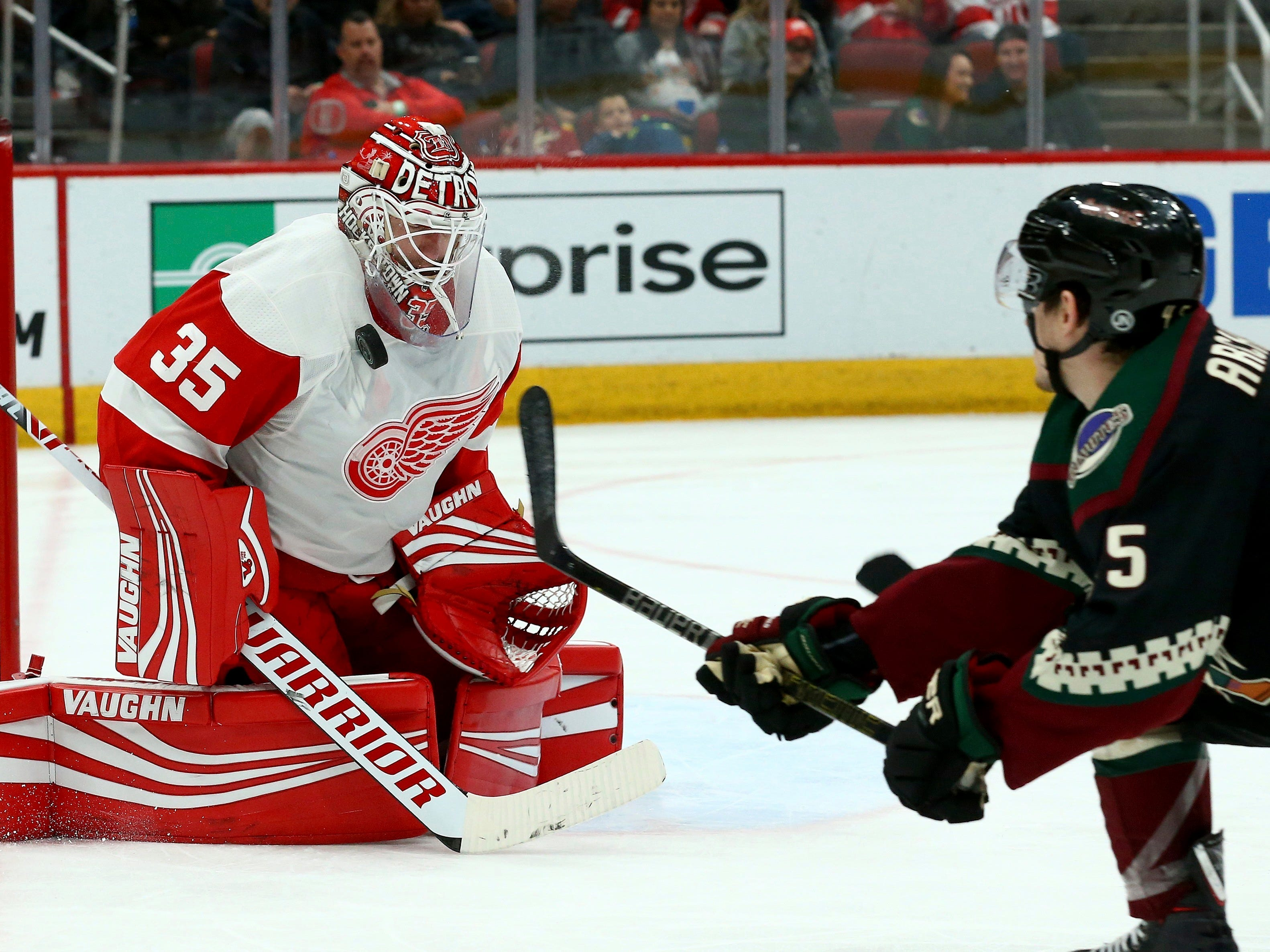 Detroit Red Wings goaltender Jimmy Howard (35) makes a save on a shot by Arizona Coyotes right wing Josh Archibald, right, during the second period Saturday, March 2, 2019, in Glendale, Ariz. (AP Photo/Ross D. Franklin)