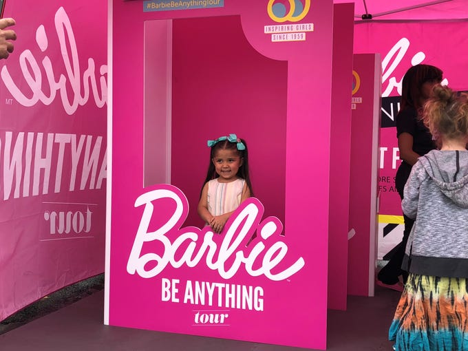 A little girl at the Barbie Be Anything tour in Glendale pretends to be a Barbie in the life-size doll box on March 2, 2019.