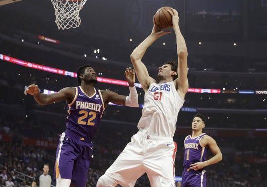 Boban Marjanovic looks to score over Deandre Ayton in NBA action.