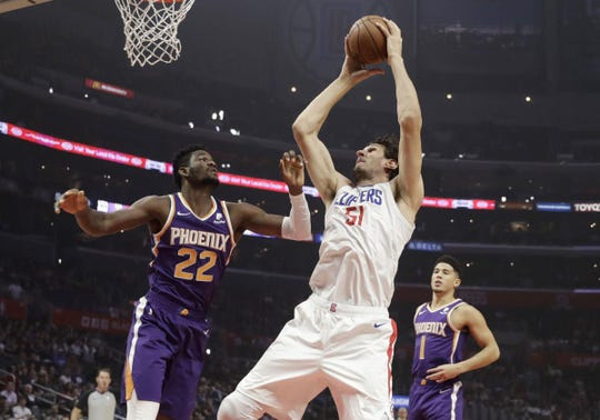 Boban Marjanovic looks to score over Deandre Ayton in NBA action.