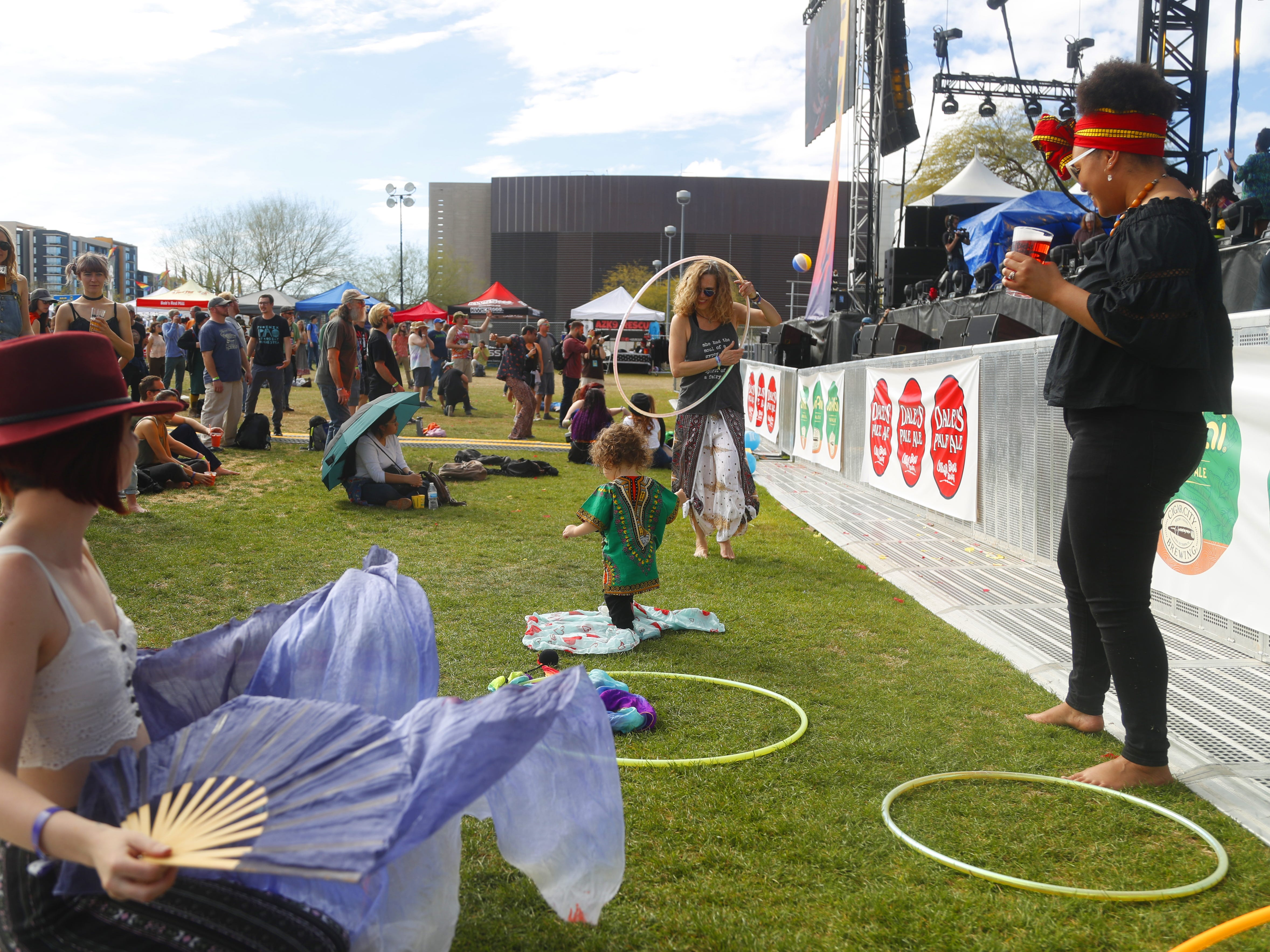 Nova Mulvaney, 1, followed by his mother Alexandra Ncube (right) make their way in front of the stage for Phoenix Afrobeat Orchestra during the McDowell Mountain Music Festival in Phoenix, Ariz. on March 2, 2019.