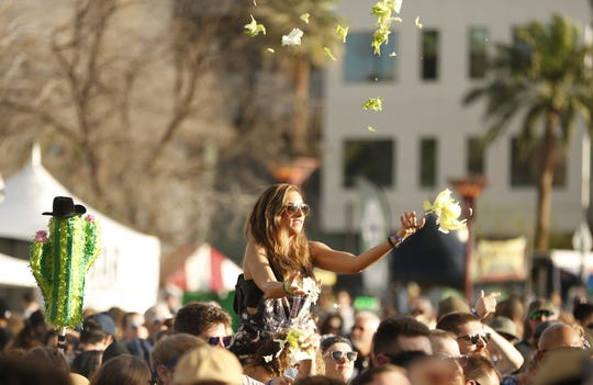 A fan throws lettuce into the air while listen to the band Lettuce during the McDowell Mountain Music Festival in Phoenix on March 2, 2019.