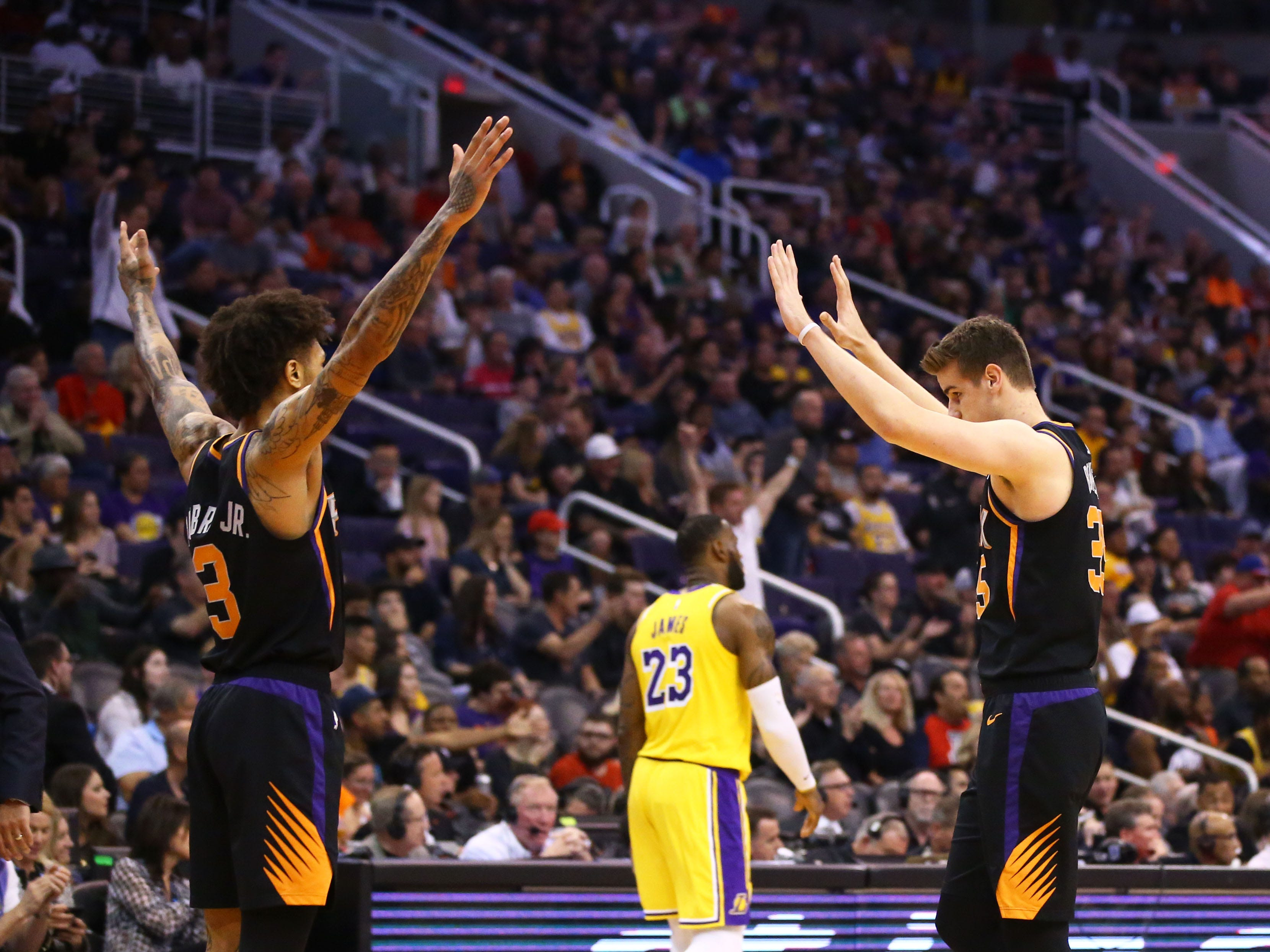 Phoenix Suns forward Kelly Oubre Jr. (3) and Phoenix Suns forward Dragan Bender (35) celebrate as Los Angeles Lakers forward LeBron James (23) walks to the bench in the second half on Mar. 2, 2019, at Talking Stick Resort Arena in Phoenix, Ariz.