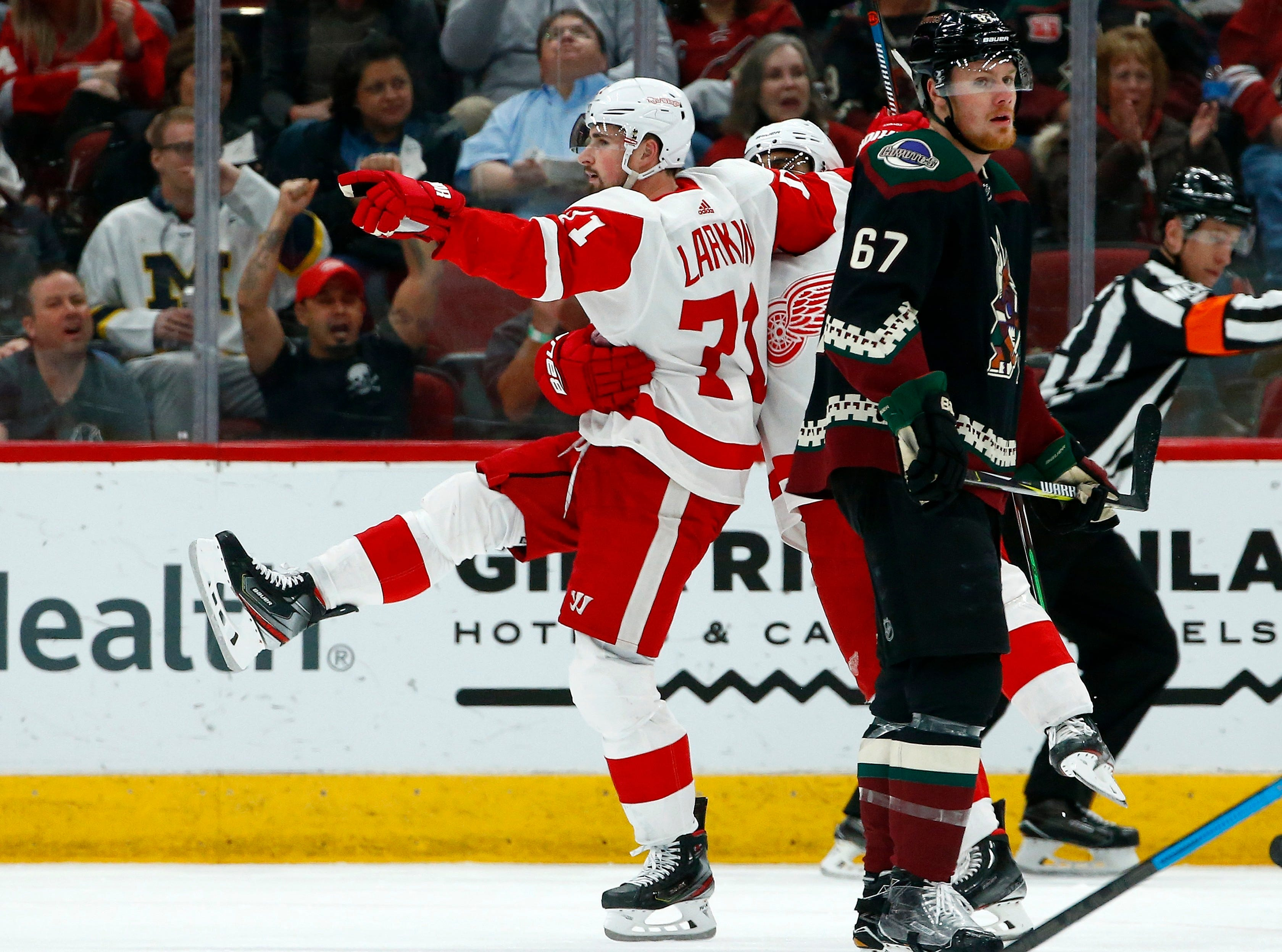 Detroit Red Wings center Dylan Larkin (71) celebrates his goal with Red Wings' Andreas Athanasiou, center, as Arizona Coyotes left wing Lawson Crouse (67) skates past during the second period of  Saturday, March 2, 2019, in Glendale, Ariz. (AP Photo/Ross D. Franklin)