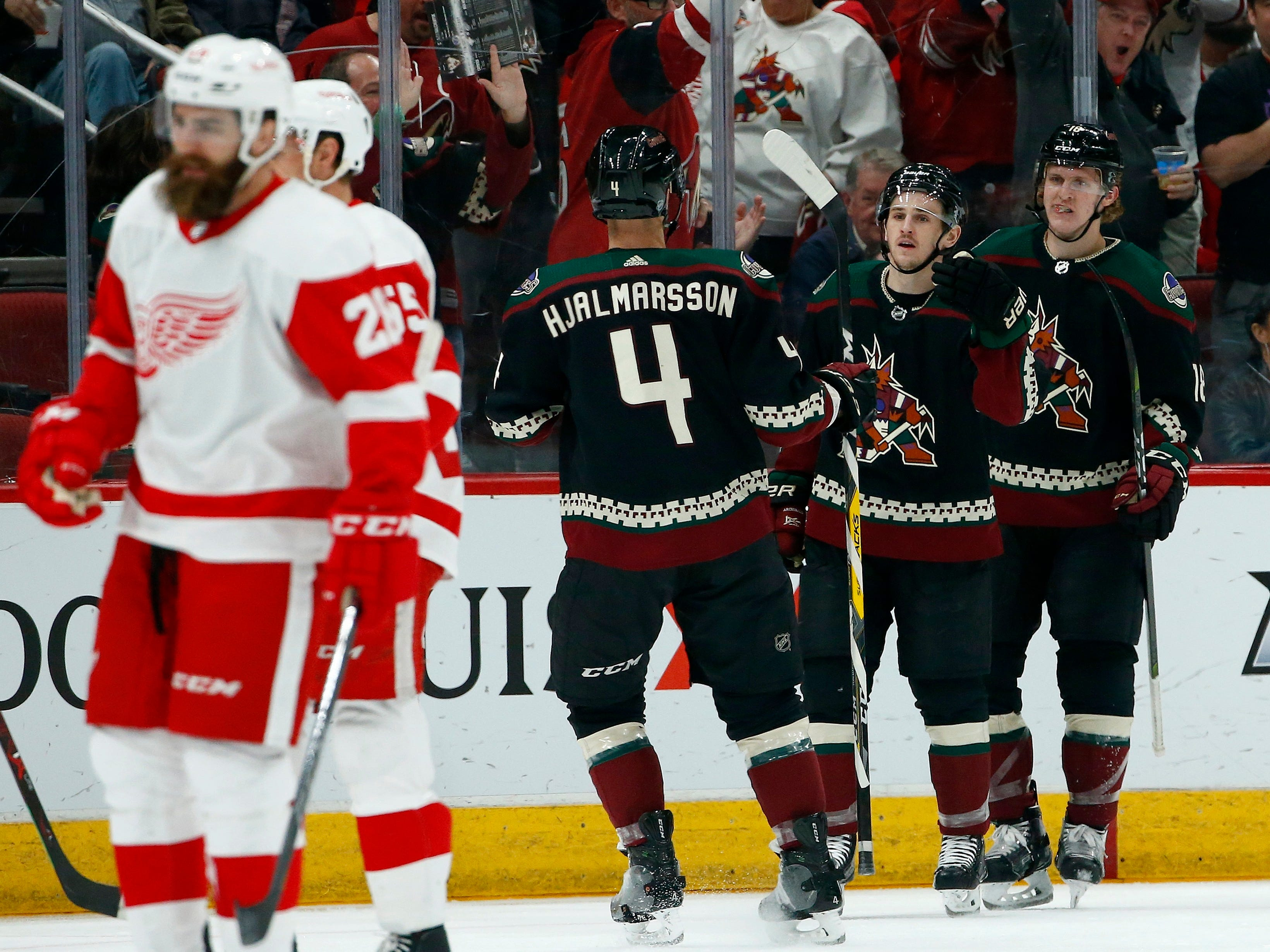 Arizona Coyotes right wing Josh Archibald, second from right, celebrates his goal with Coyotes center Christian Dvorak (18) and defenseman Niklas Hjalmarsson (4) as Detroit Red Wings right wing Luke Witkowski, left, and defenseman Niklas Kronwall, second from left, skate to the bench during the first period Saturday, March 2, 2019, in Glendale, Ariz. (AP Photo/Ross D. Franklin)