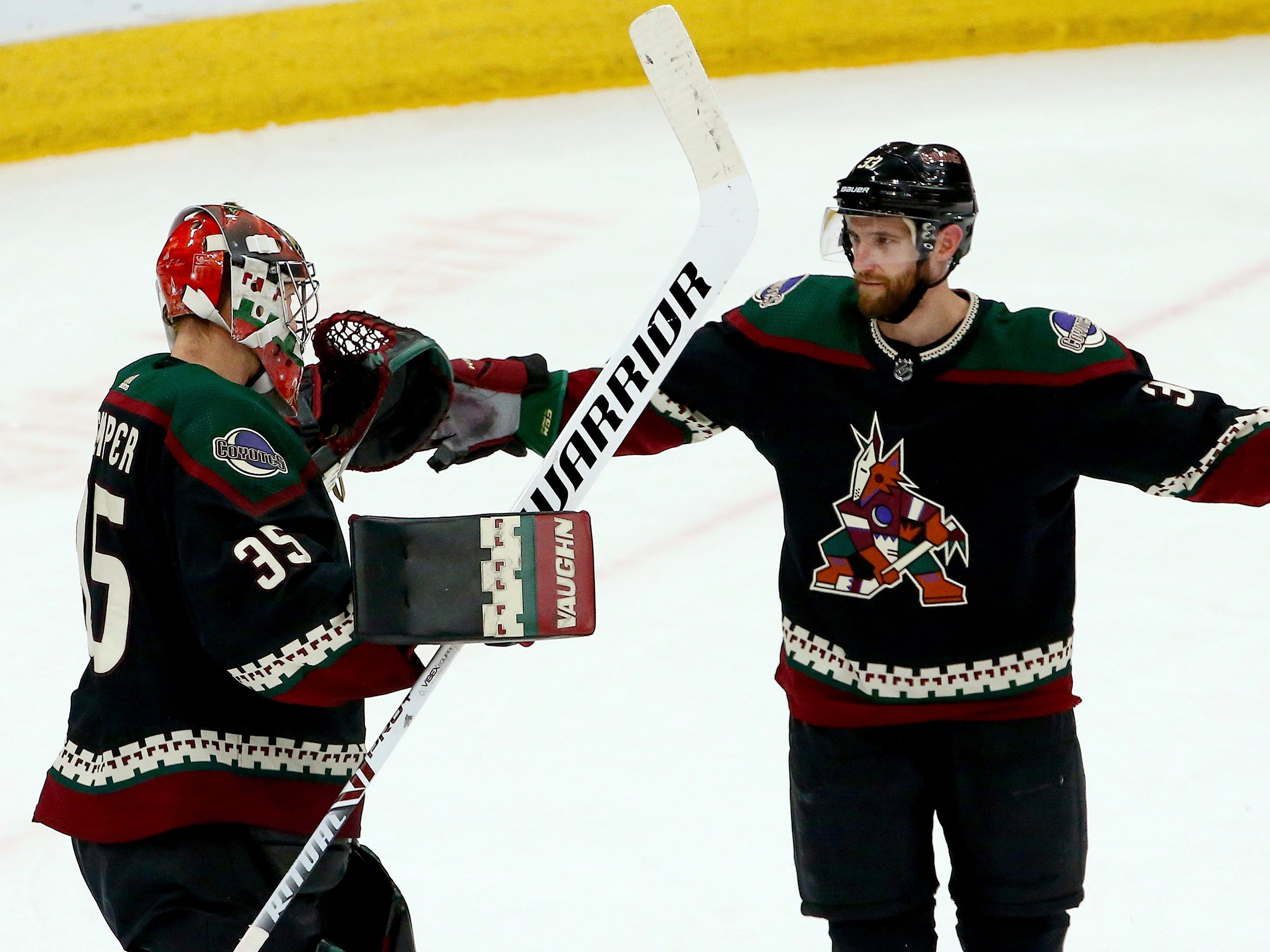 Arizona Coyotes goaltender Darcy Kuemper (35) celebrates a win against the Detroit Red Wings with defenseman Alex Goligoski, right, as time expires in the third period Saturday, March 2, 2019, in Glendale, Ariz. (AP Photo/Ross D. Franklin)