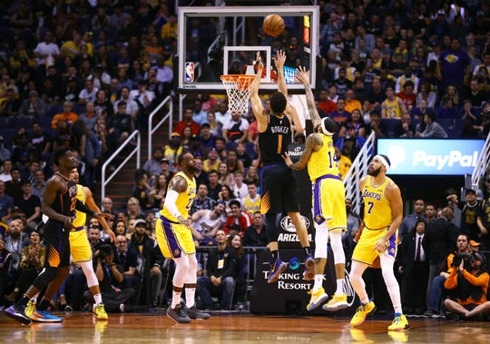 Phoenix Suns guard Devin Booker (1) shoots and scores past Los Angeles Lakers forward Brandon Ingram (14) in the second half on Mar. 2, 2019, at Talking Stick Resort Arena in Phoenix, Ariz.