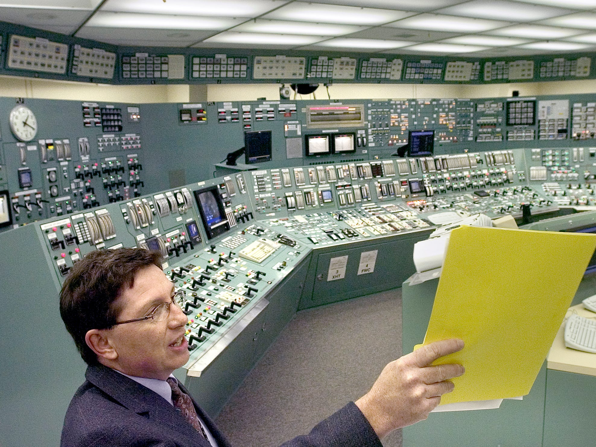 Ralph DeSantis, site communications manager, right, talks with media from the training control room March 26, 2004. It is a mirror of the real thing and is not connected to the plant.