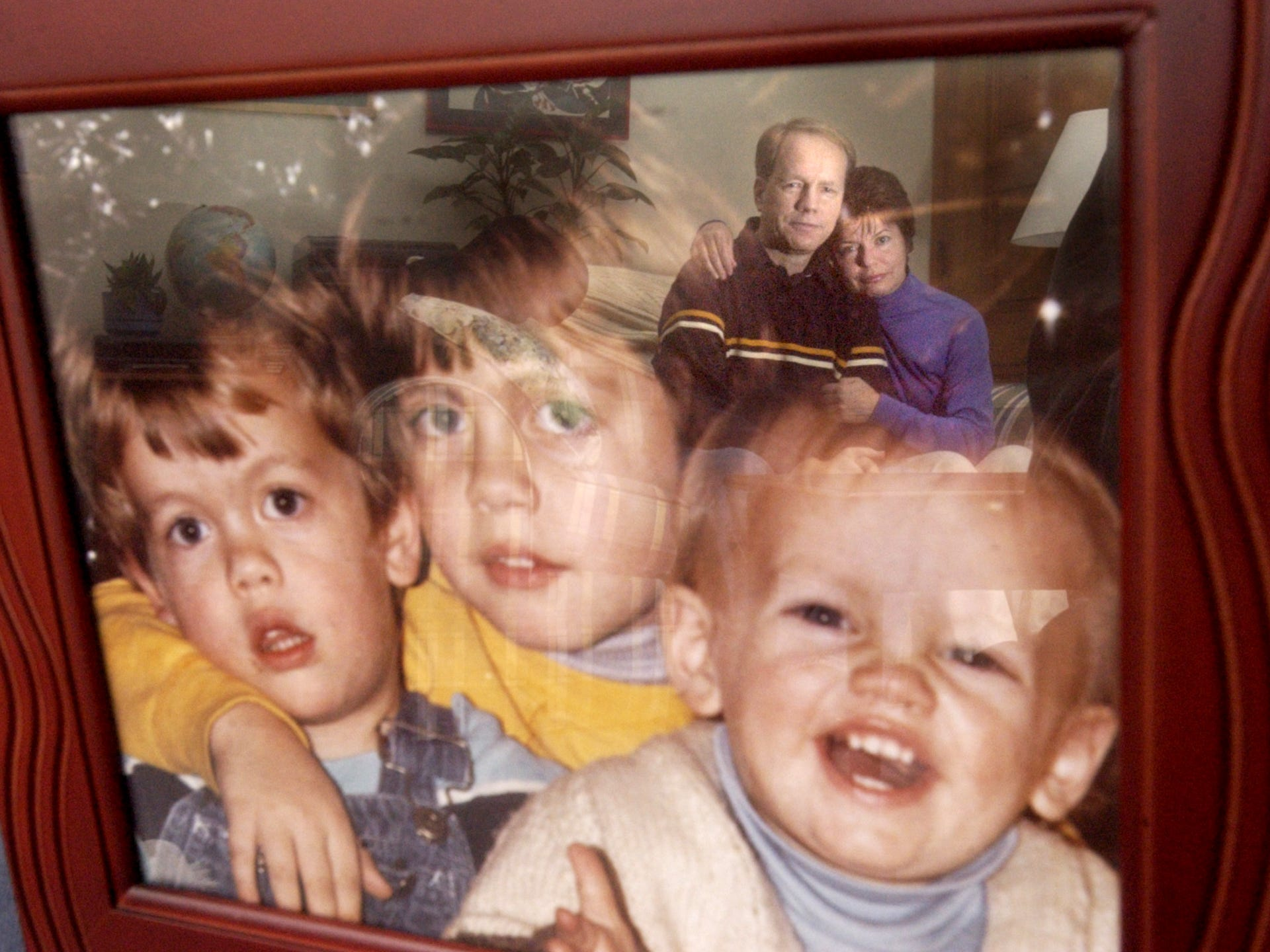 In a picture taken in 2004, Dean and Norma Newhouse are reflected in a 1977 photograph of the Fairview Township couple's three sons. In the days following the accident at TMI, the family - including, from left, Eric, Marty and Ben - went to Connecticut until the accident at Three Mile Island was under control.