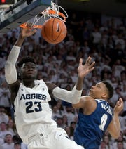 Utah State center Neemias Queta (23) dunks against Nevada's Tre'Shawn Thurman on Saturday in Logan, Utah.