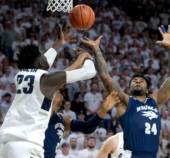 Utah State's Neemias Queta (23) fights for a rebound against the Wolf Pack's Jordan Caroline on Saturday night.
