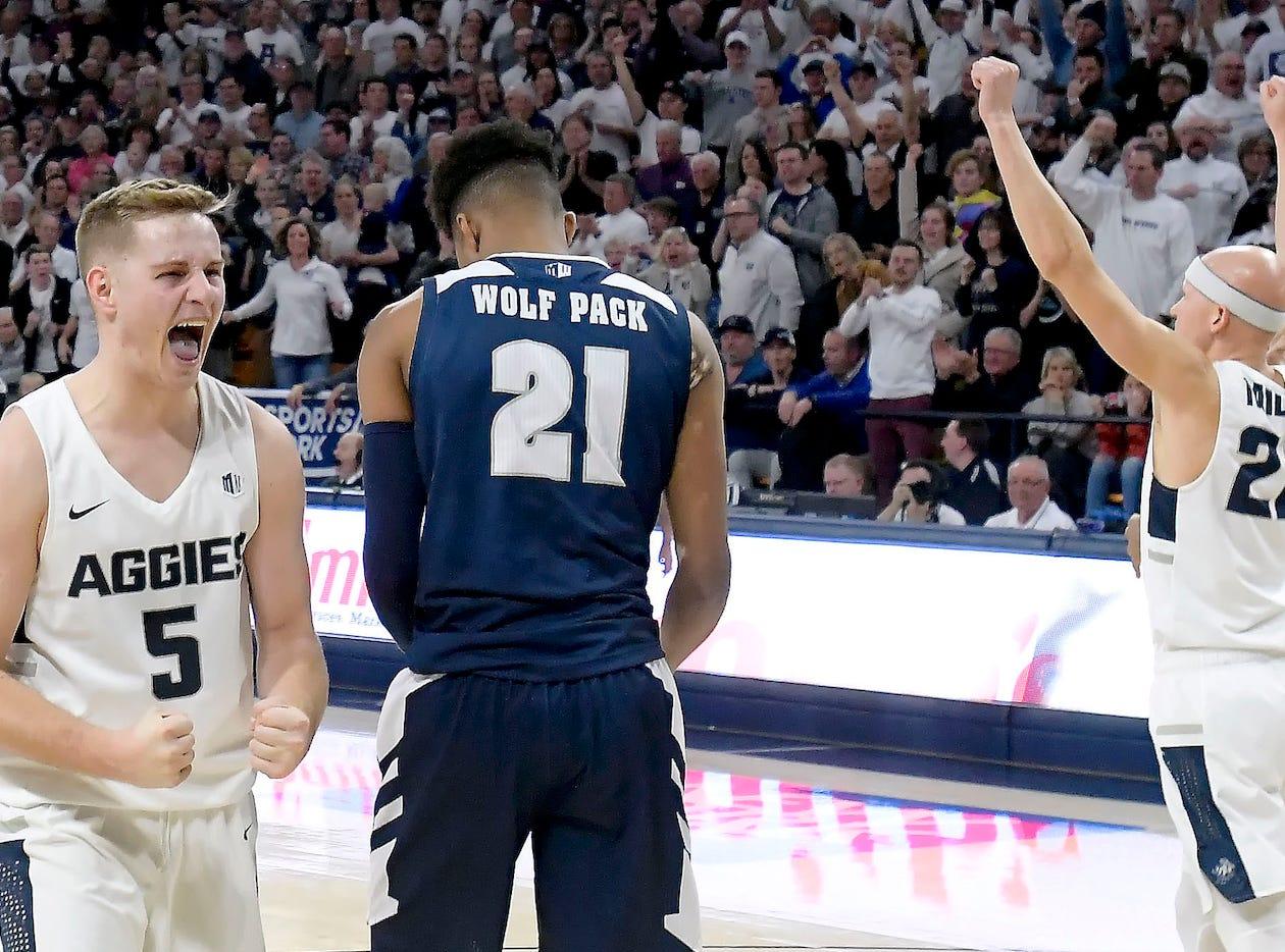 Utah State's Sam Merrill (5) and Brock Miller (22) celebrate next to Nevada's Jordan Brown after Merrill drew a charge call Saturday night.
