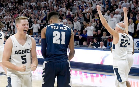 Utah State's Sam Merrill (5) and Brock Miller (22) celebrate next to Nevada's Jordan Brown after Merrill drew a charge call Saturday night.