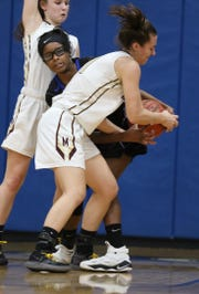 Pittsford Mendon's Alana Fursman grabs the ball and tries to steal it from Brockport's Shinya Lee.