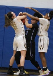 Brockport's Doralis Allen gets trapped between Pittsford Mendon's Katie Bischoping and Anaya Coleman.  Bischoping got her hands on the ball and stripped it out of Allen's.