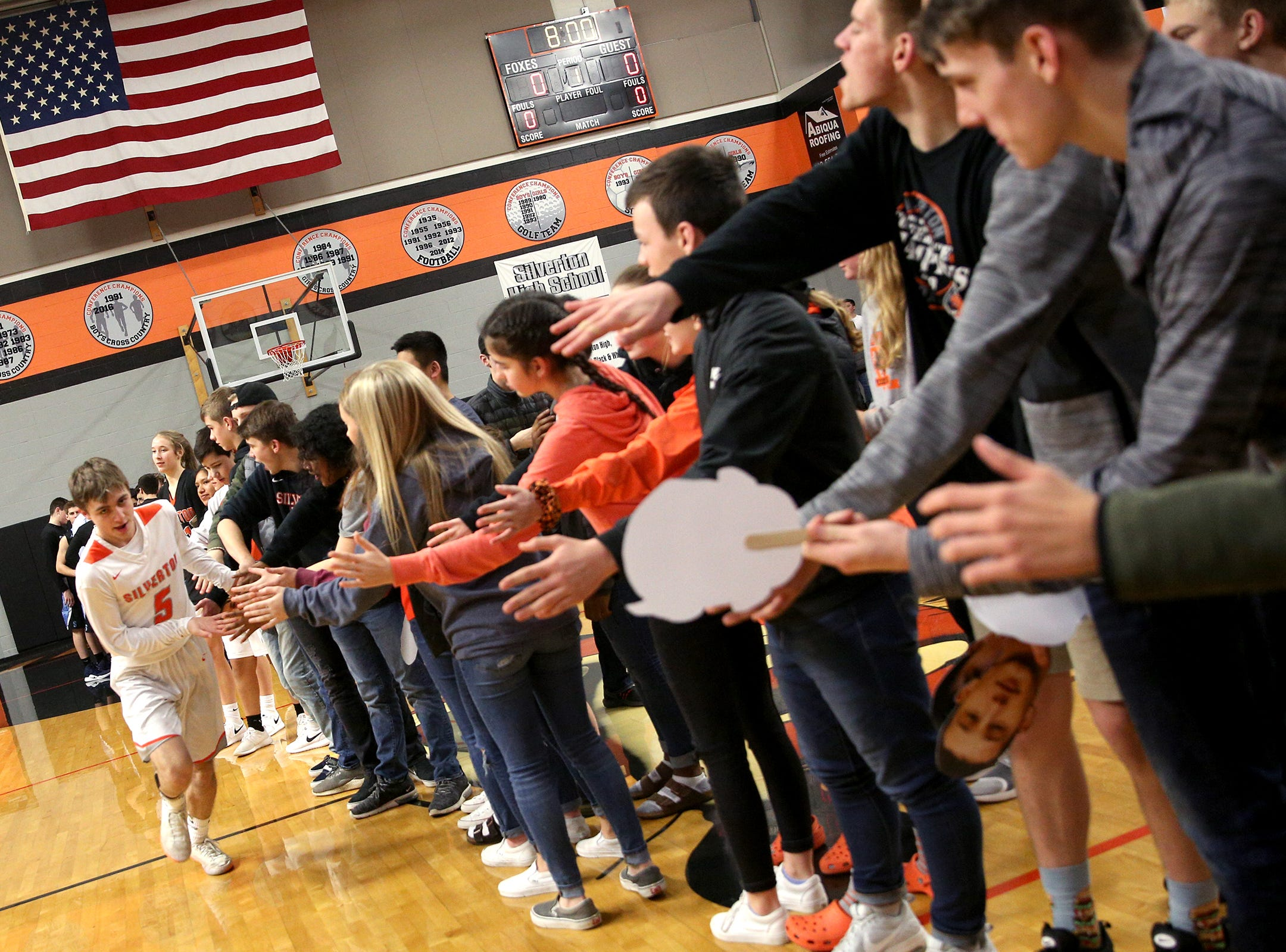 Silverton's Drake Ulven (5) high-fives a row of students as he's introduced in the starting lineup before the Silverton vs. Springfield boys basketball OSAA state playoffs game at Silverton High School in Silverton on Saturday, March 2, 2019.