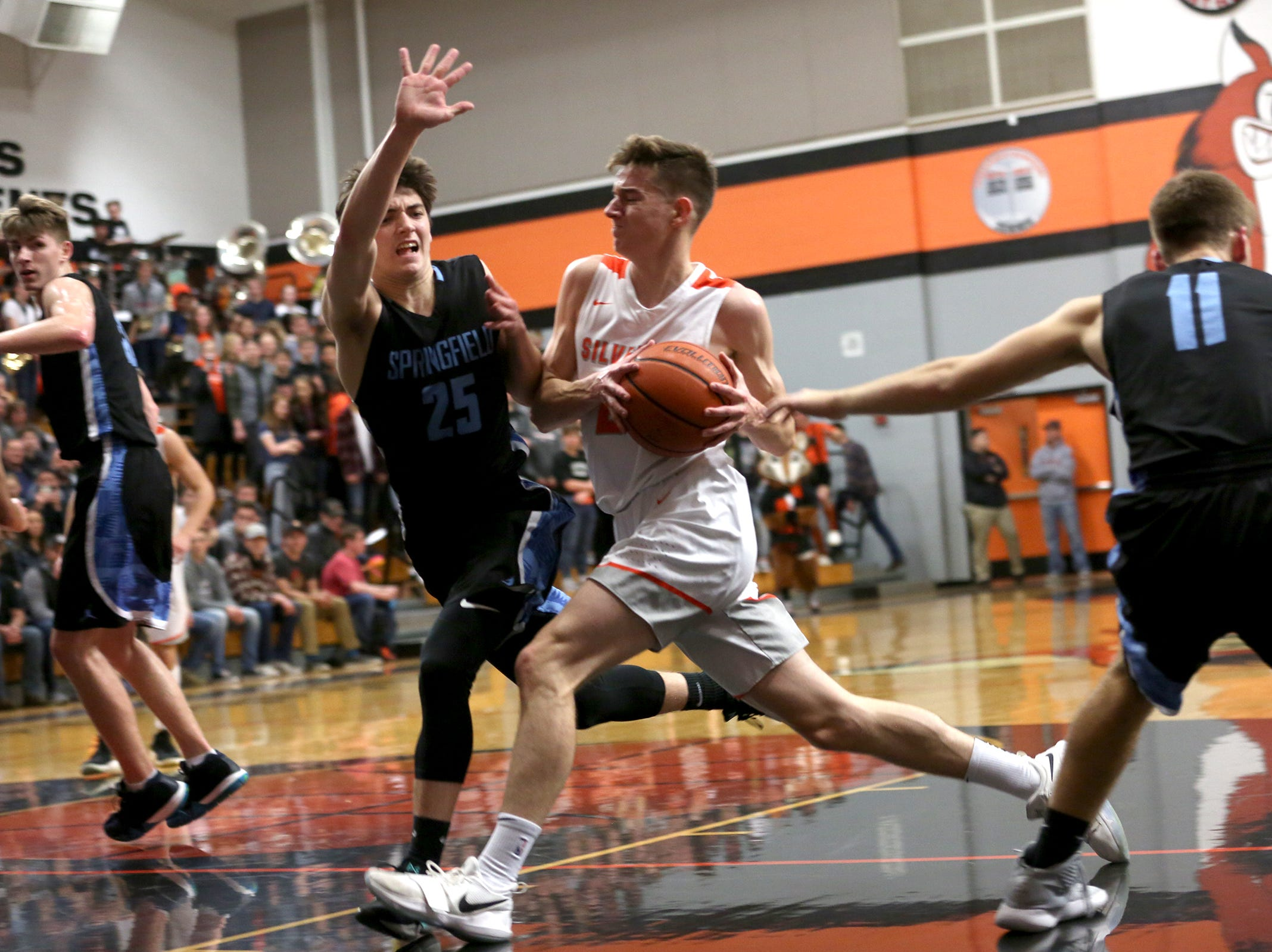 Silverton's Josiah Roth (21) forces his way into the paint during the Silverton vs. Springfield boys basketball OSAA state playoffs game at Silverton High School in Silverton on Saturday, March 2, 2019.
