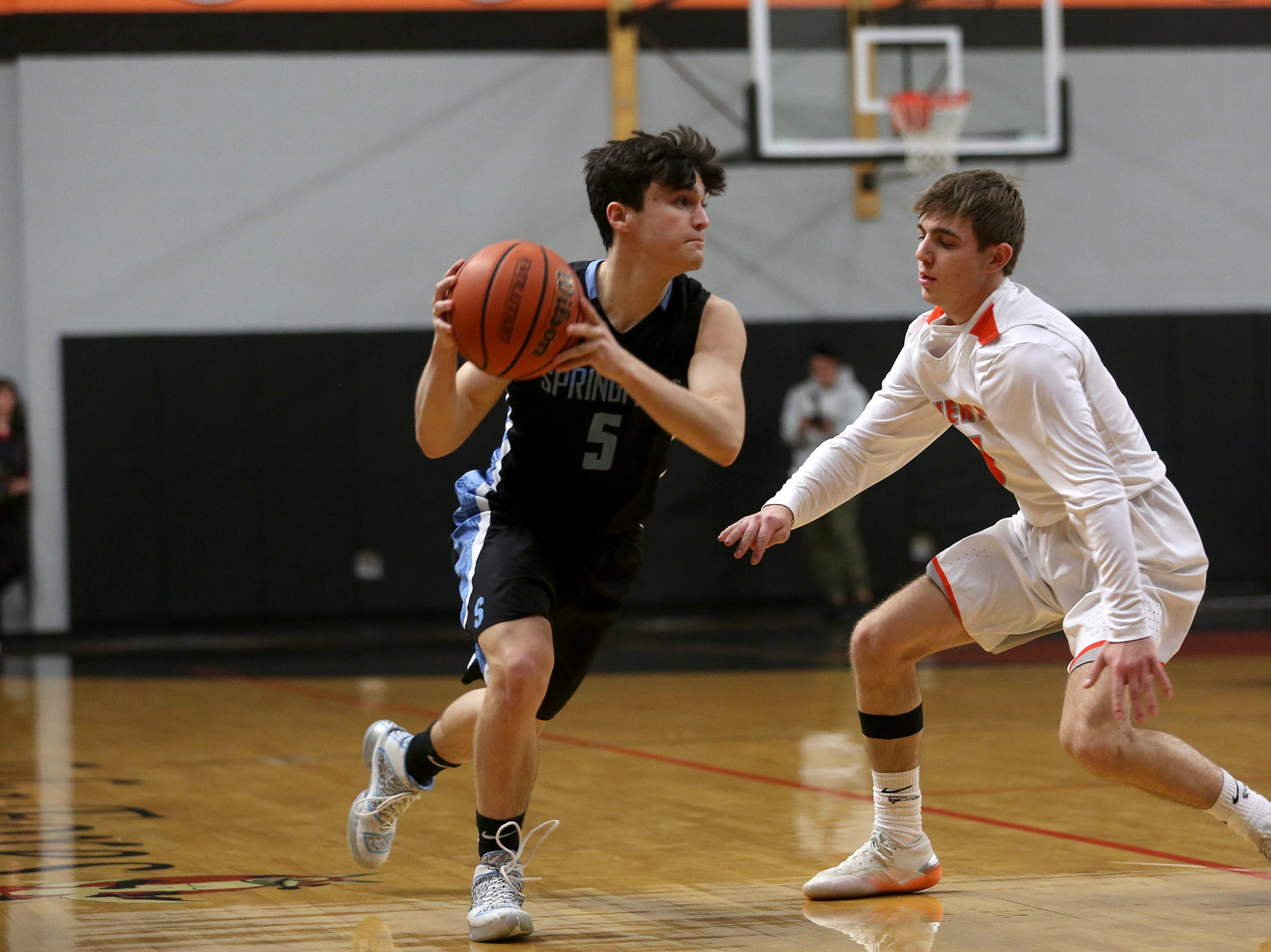 Springfields' Zack Sorber (5) attempts to make his way around Silverton's Drake Ulven (5) during the Silverton vs. Springfield boys basketball OSAA state playoffs game at Silverton High School in Silverton on Saturday, March 2, 2019.