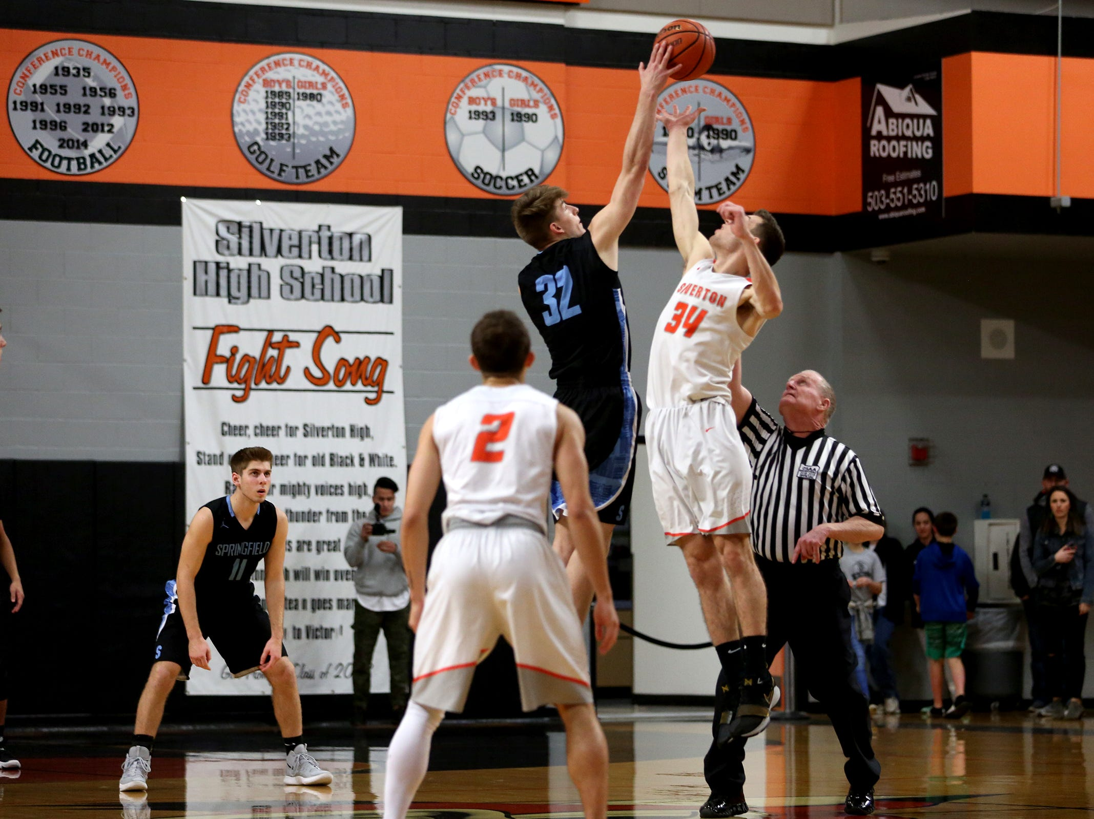 Silverton's Levi Nielsen (34) and Springfield's Zach Brown (32) go up at tipoff during the Silverton vs. Springfield boys basketball OSAA state playoffs game at Silverton High School in Silverton on Saturday, March 2, 2019.