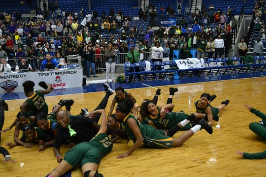 """Captain Shreve Gator players dive on the floor in celebration as they receive their championship trophy. The Gators captured the 5A state title with a 66-57 win over Denham Springs at the 2019 Allstate Sugar Bowl/LHSAA """"Marsh Madness"""" Tournament Saturday at the Rapides Parish Coliseum in Alexandria."""
