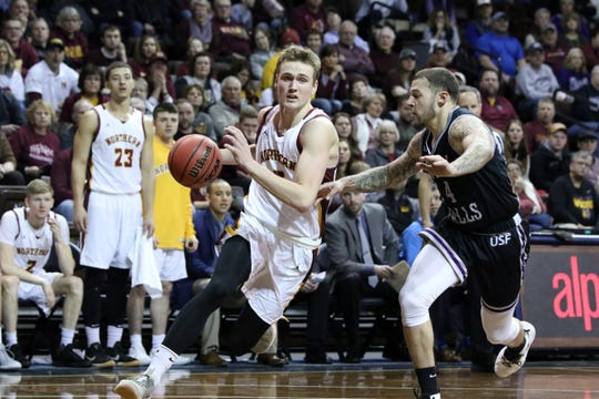 Northern State's Andrew Kallman slips past the defense by Trevon Evans of USF during Sunday's NSIC quarterfinal game at the Pentagon.