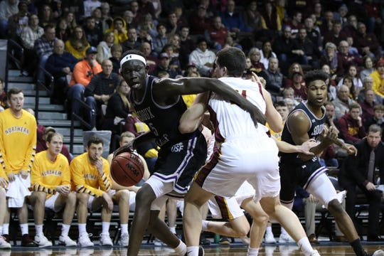 Tessy Pal of USF hooks Gabe King of Northern State during Sunday's NSIC quarterfinal game at the Pentagon.