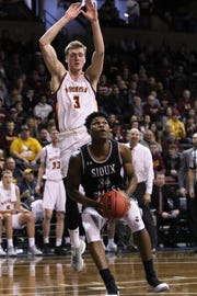 USF's Troy Houghton eyes the basket as Andrew Kallman of Northern State looks to block his shot during Sunday's NSIC quarterfinal game at the Pentagon.
