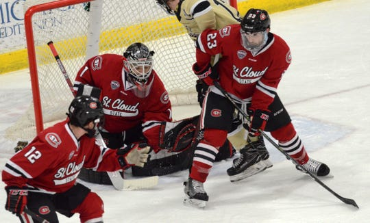 St. Cloud State's Jack Ahcan and Robby Jackson defend the net along with goalie  Jeff Smith in Saturday's NCHC game against Western Michigan.
