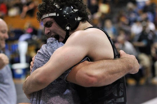 Chiles sophomore Kyle McGill hugs wrestling coach James Marschka after McGill qualified for state at 170 pounds during the Region 1-2A wrestling tournament at Chiles on March 2, 2019.