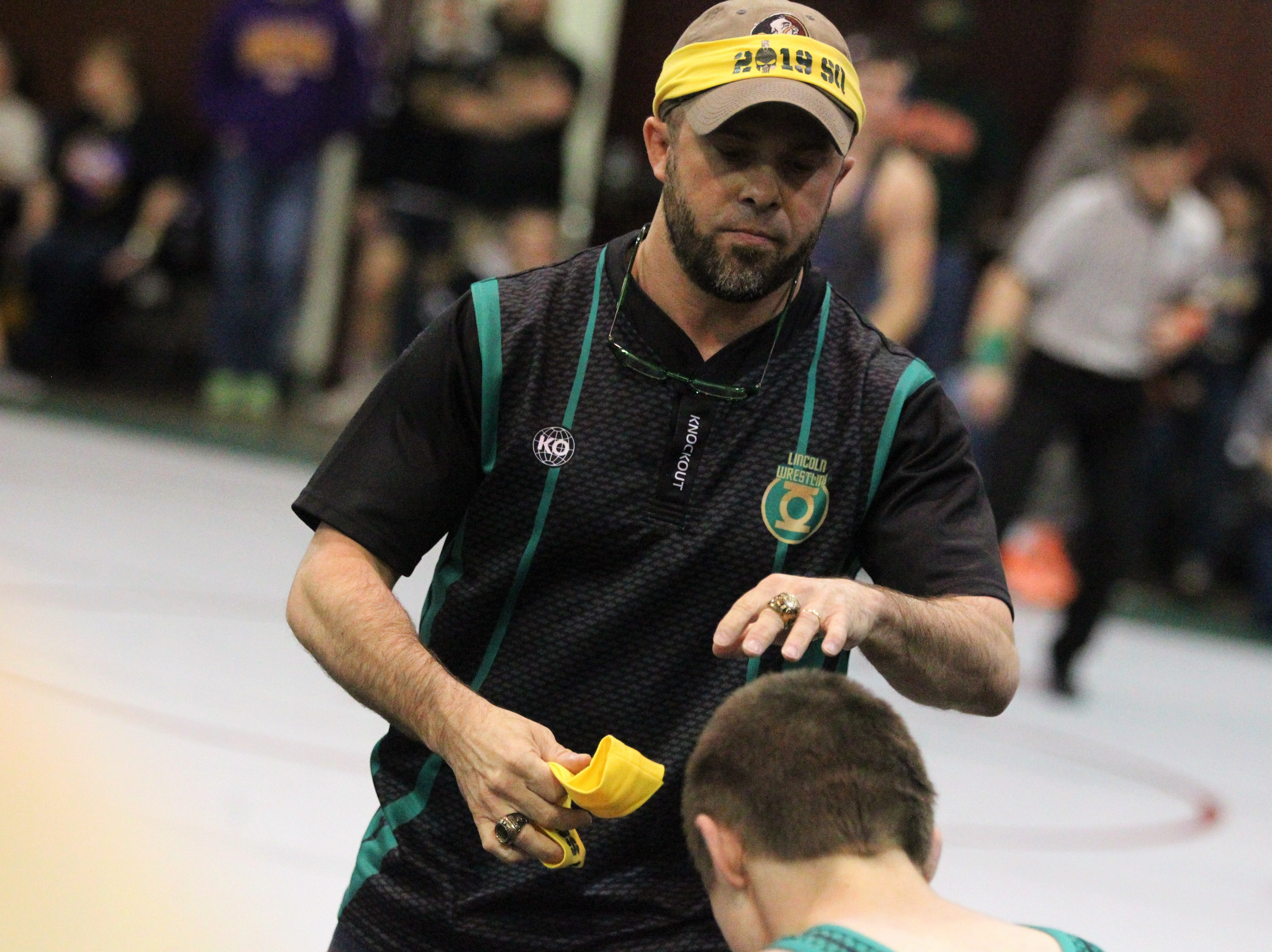 Lincoln wrestling coach Mike Crowder knights senior Mark Munroe (113 pounds) as a state qualifier during the Region 1-2A wrestling tournament at Chiles on March 2, 2019.