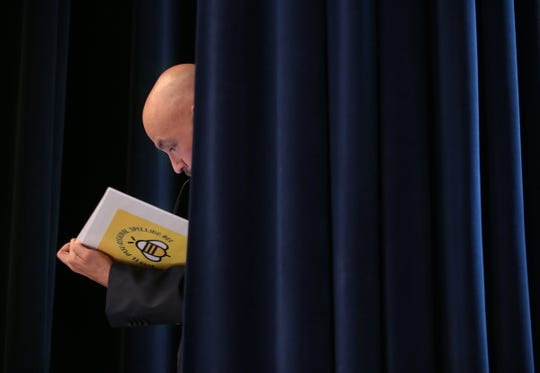 2019 El Paso Regional Spelling Bee pronouncer Dr. Richard Pineda looks through the official book of word between rounds Saturday at Bowie High School.