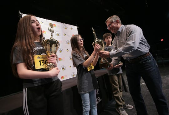 Penelope Moore is presented her first place trophy Saturday at the 2019 El Paso Regional Spelling Bee.