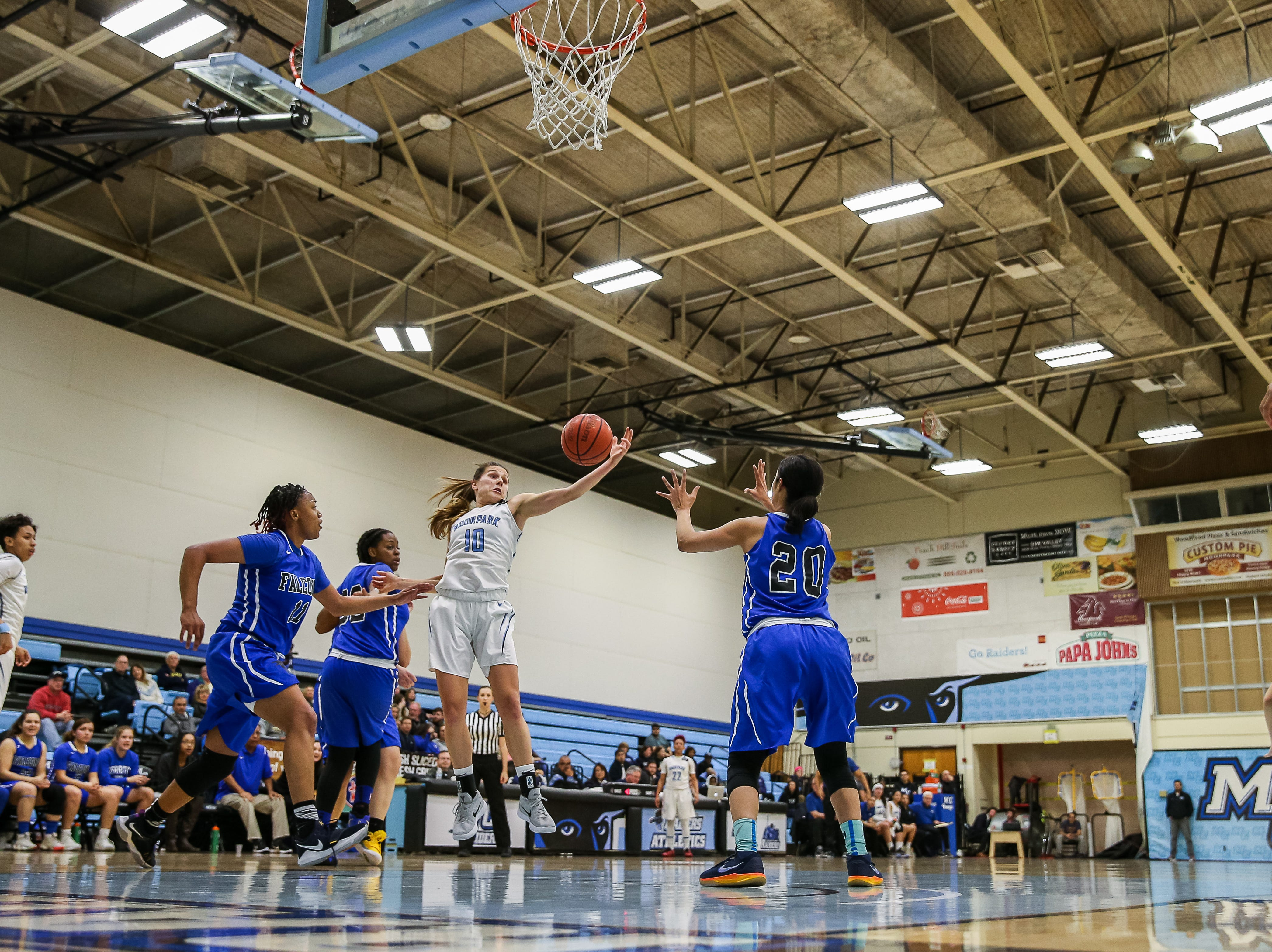 Moorpark College's Emily Herring attempts to reel in an offensive rebound amid a triangle of Cerritos College defenders during the Raiders' 86-56 win in a Southern California regional semifinal game Saturday night at Moorpark College. Herring had 16 points and 10 rebounds.