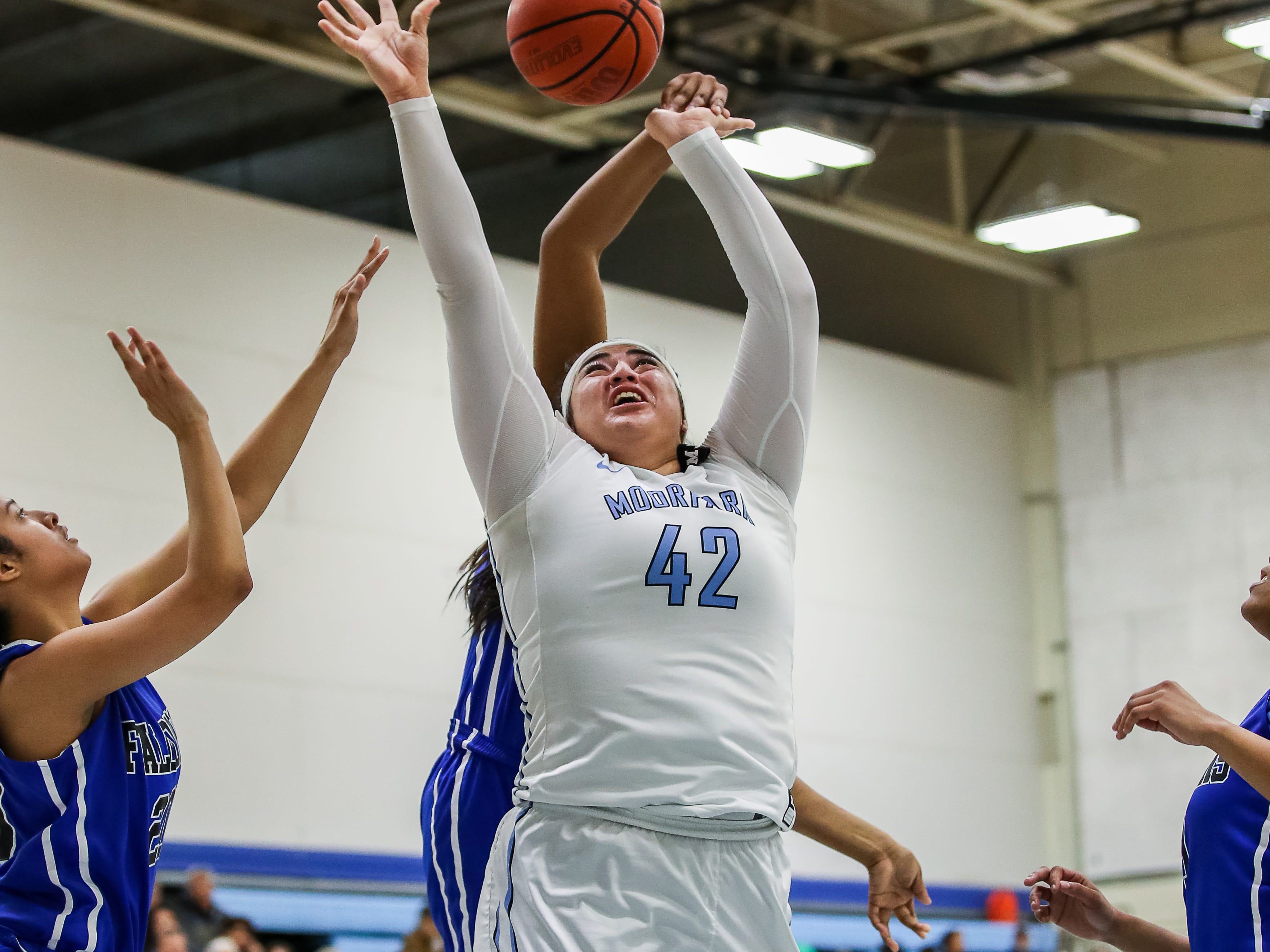 Moorpark College's Barbara Rangel is fouled while going up for a layup during the Raiders' 86-56 win over Cerritos in a Southern California regional semifinal game Saturday night at Moorpark College. Rangel had 19 points and 21 rebounds.