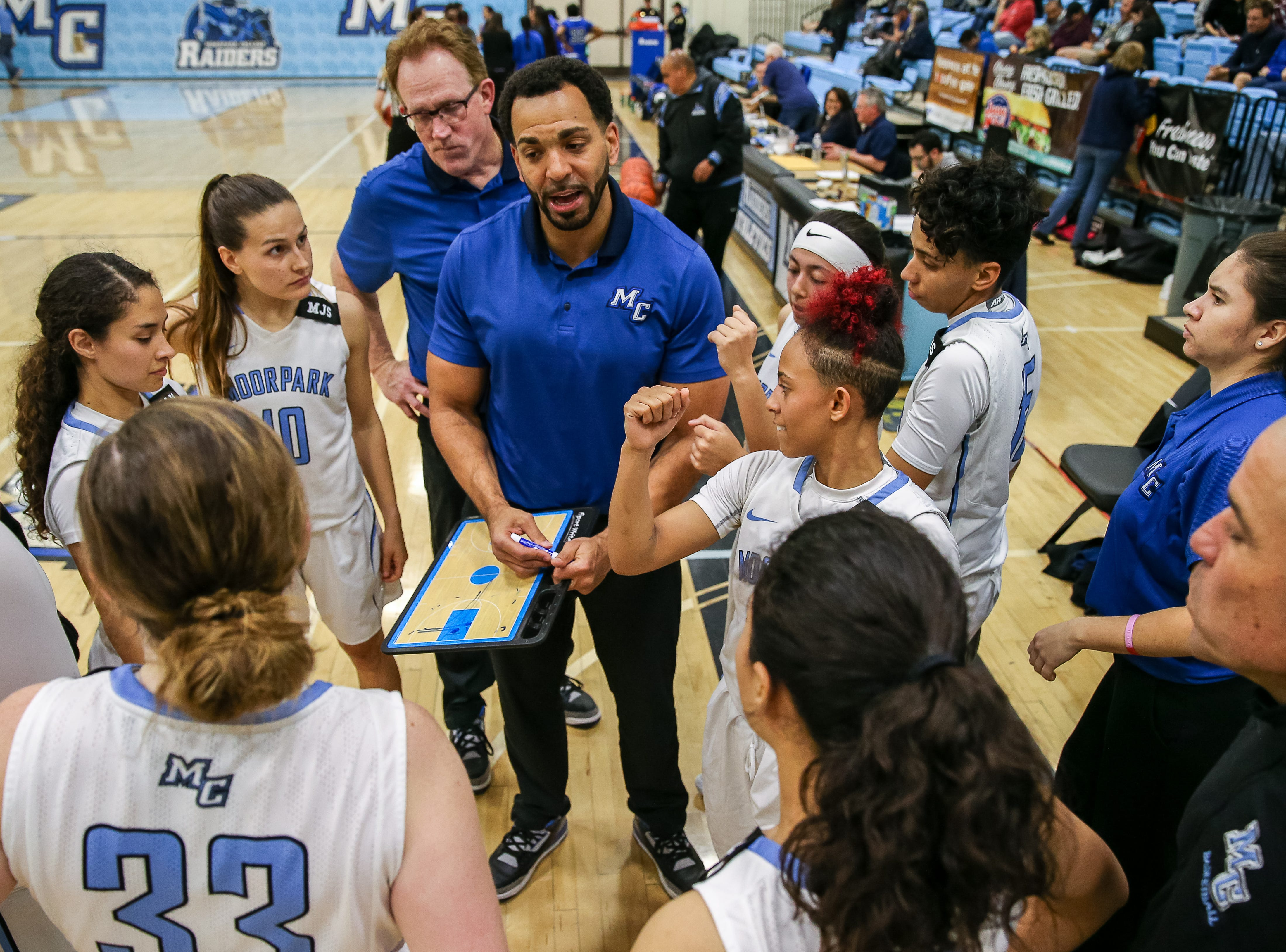 Moorpark College head coach Kenny Plummer gathers his players for some game planning during the Raiders' 86-56 win over Cerritos in a Southern California regional semifinal game Saturday night at Moorpark College.