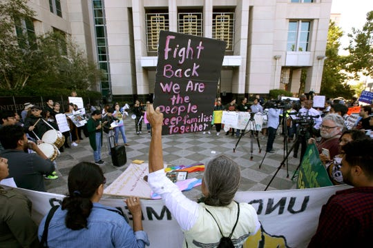 """In this June 20, 2018, photo, protesters demonstrate outside the federal courthouse in Sacramento, where a judge heard arguments over the U.S. Justice Department's request to block three California laws that extend protections to people in the country illegally. The Justice Department told The Associated Press at the end of February 2019 that 28 jurisdictions, including Sacramento, that were targeted in 2017 over what it considered """"sanctuary"""" policies have been cleared for law enforcement grant funding."""