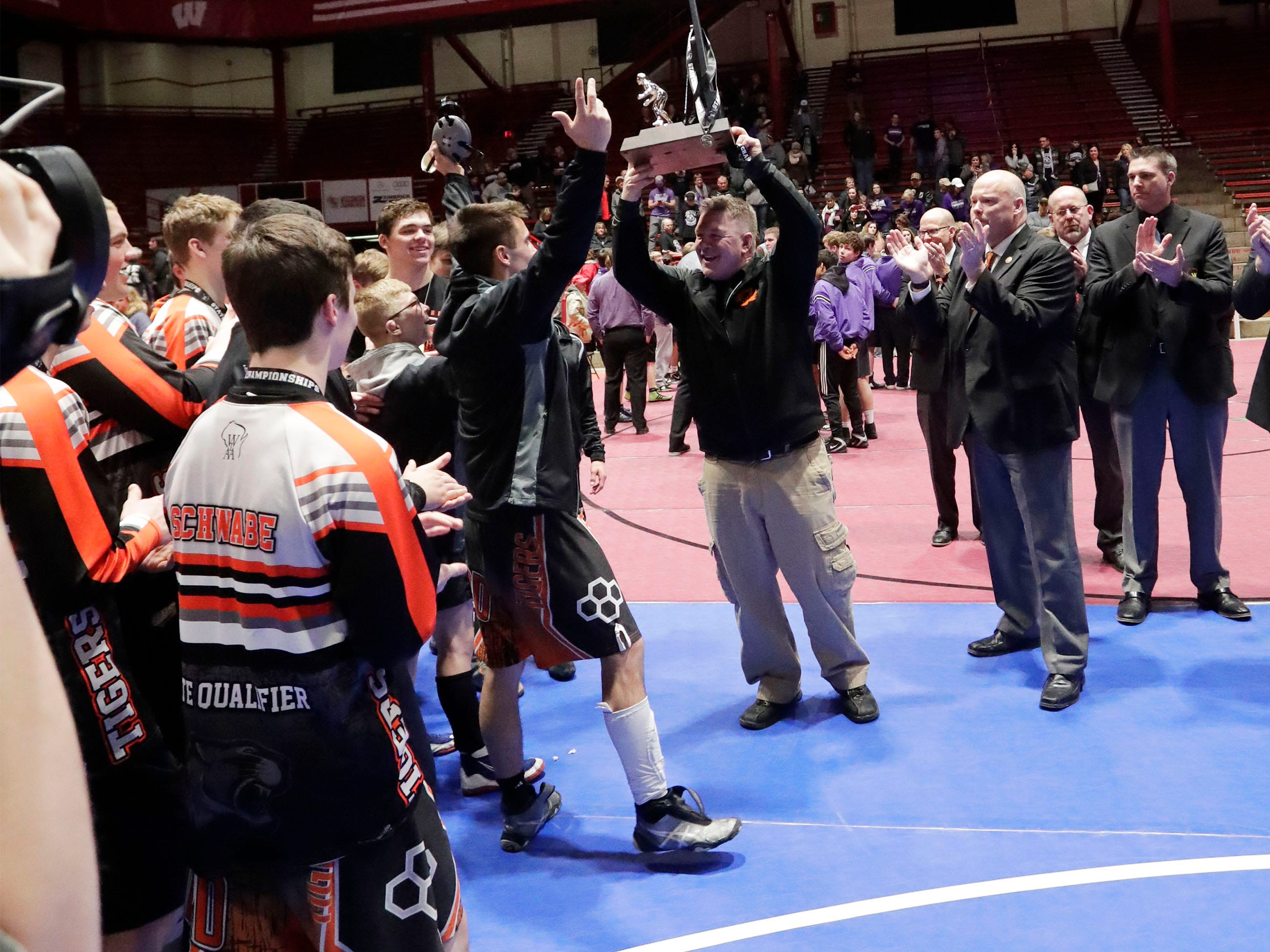 Stratford head coach Joe Schwabe, center, holds high the second place trophy following their defeat from Fennimore for the state team title, Saturday, March 2, 2019, in Madison, Wis.