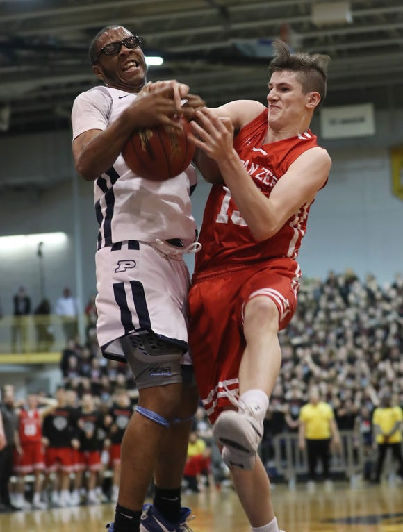 Poughkeepsie's Jahquel Harvard (12) and  Tappan Zee's Charlie Harrison (15) battle for a rebound during the Section 1 Class A championship game at Pace University in Pleasantville March 2, 2019. Poughkeepsie won the game 47-42.