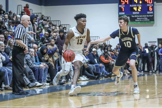 Sanford forward Jyare Davis (13) makes a move against Salesianum's Jack Brown during the Warriors' 59-40 win in the quarterfinals of the DIAA Boys Basketball Tournament on Saturday night at St. Georges.