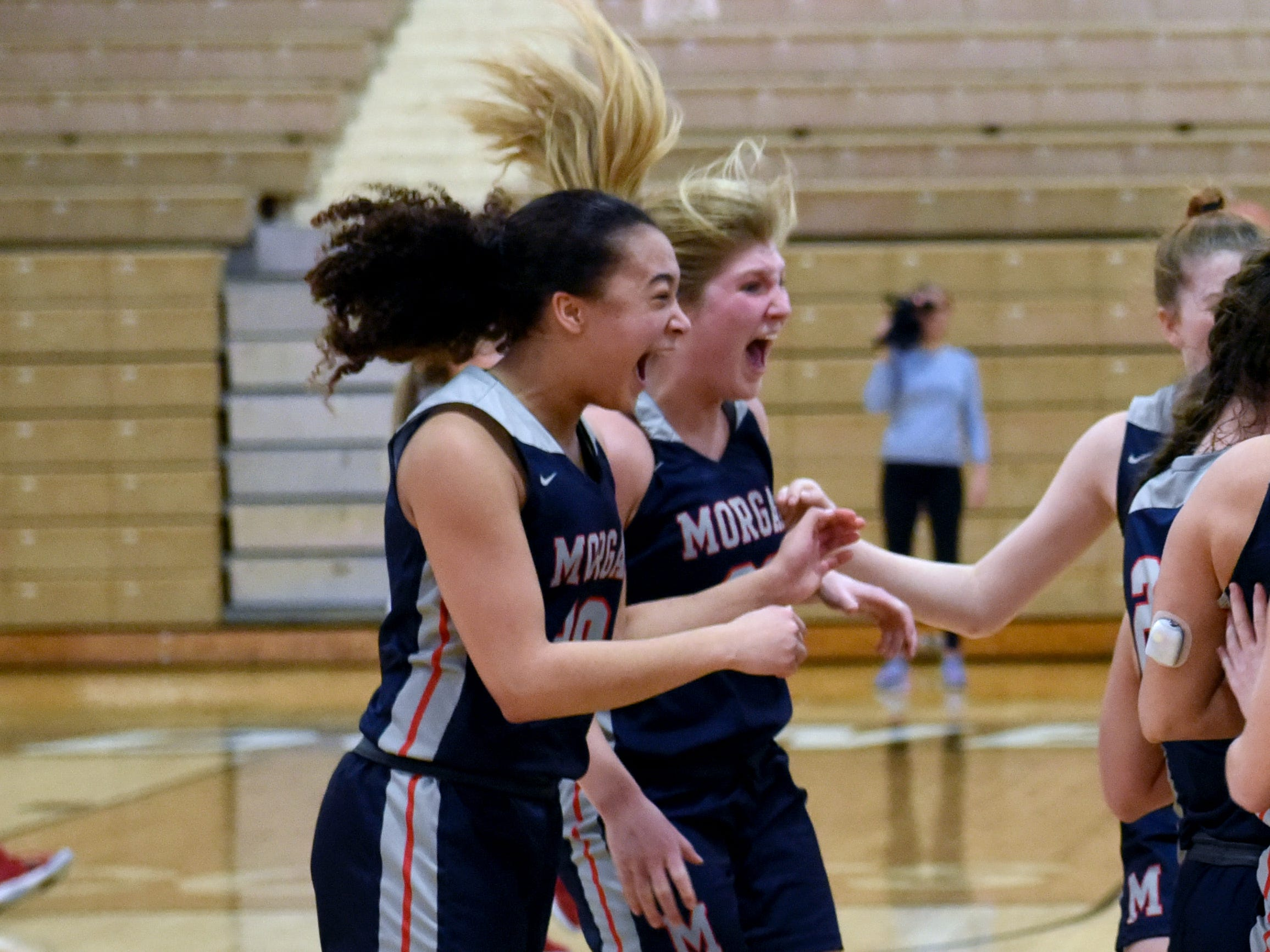 Morgan's Heaven Williams, left, and Kara Hopkins celebrate on the court following a 46-44 win against Bellaire on Saturday in a Division III district final at Meadowbrook High School.