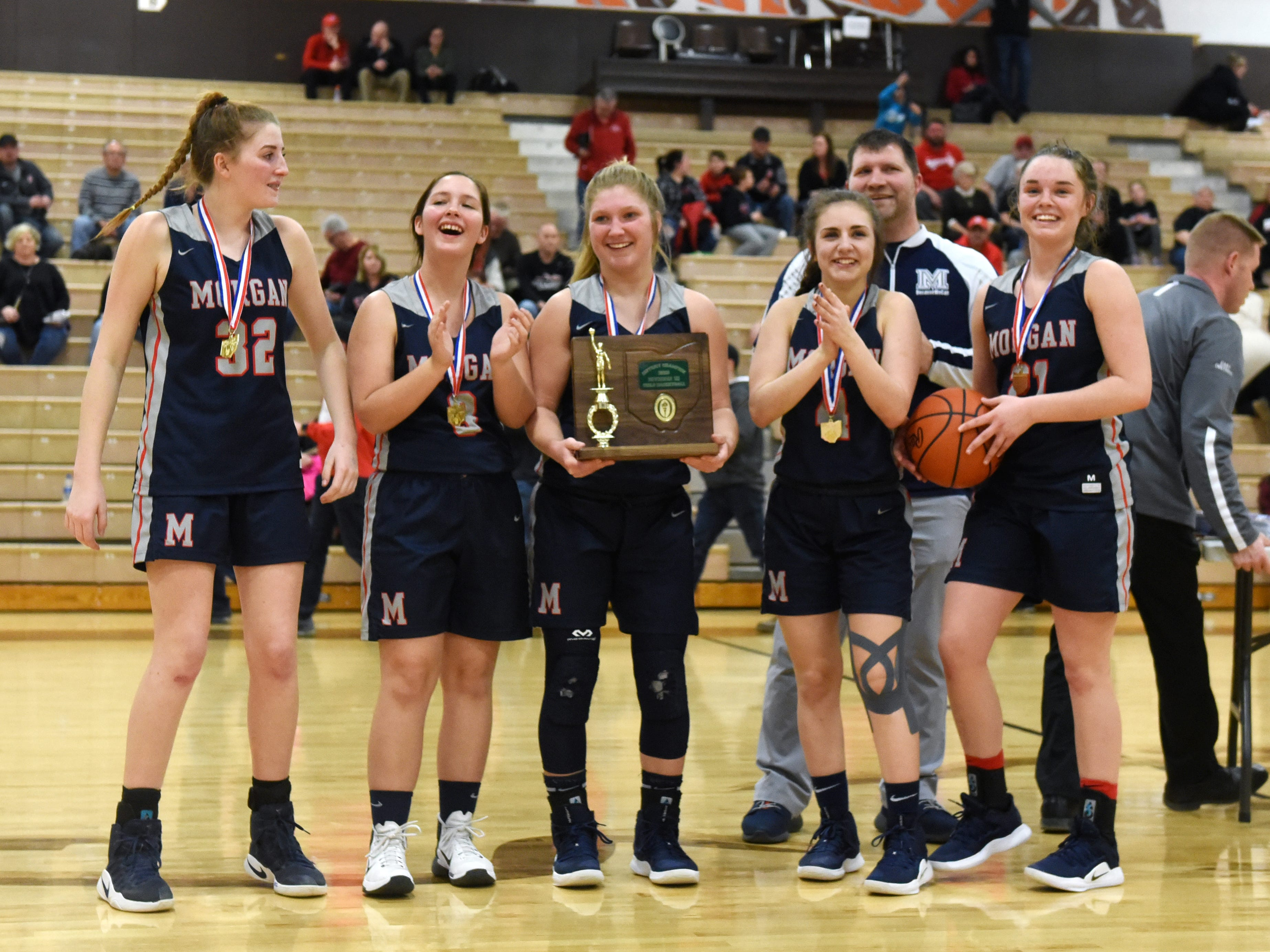 Morgan's seniors stand with the district championship trophy it earned following a Division III district final win against Bellaire on Saturday at Meadowbrook.