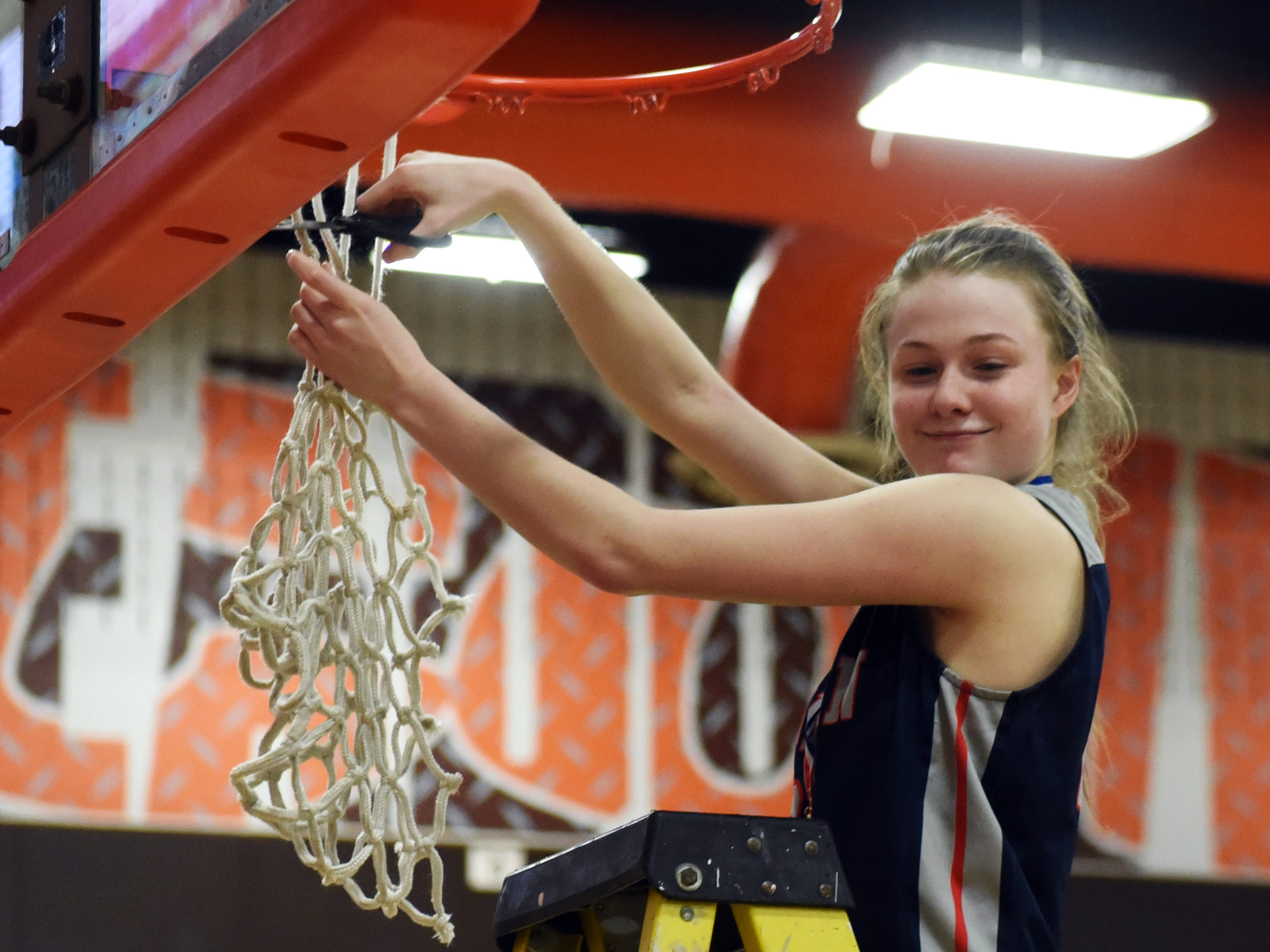Morgan's Tori Miller helps cut down the net following a 46-44 win against Bellaire in a Division III district final at Meadowbrook.